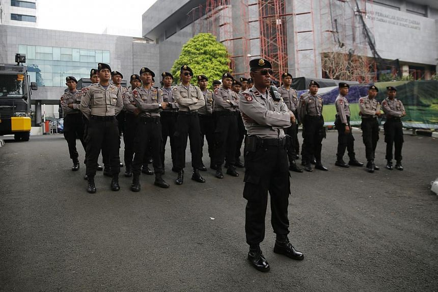Indonesian police standing guard outside city hall during a small protest in Jakarta on Nov 17, 2014. The inauguration of Jakarta's first Christian governor in 50 years was postponed to next week to allow for a presidential decree on his appointment,