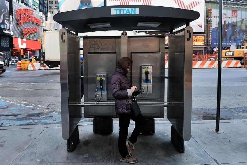 A woman uses her cell phone while leaning on a public phone booth in New York. Thousands of high-tech terminals offering free Wi-Fi and other services will soon replace the city's remaining fleet of seldom-used pay phones. -- PHOTO: AFP