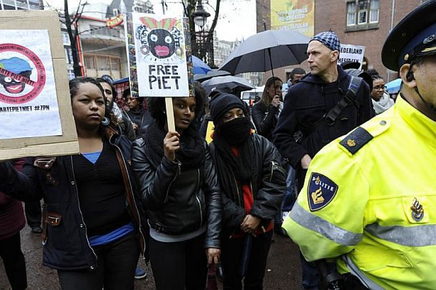 """People gather during a demonstration against the tradition of 'Zwarte Piet' or """"Black Pete"""" the black-faced companion of Sinterklaas or Sain Nicholas in Amsterdam, on Nov 16, 2014. The figure of Black Pete, the traditional black-faced companion of Sa"""