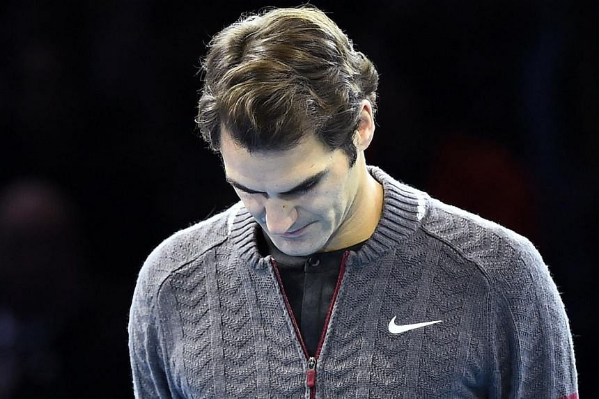 Roger Federer of Switzerland waits to announce that he is injured and unfit to play Novak Djokovic of Serbia in the men's singles final tennis match at the ATP World Tour Finals at the O2 in London, on Nov 16, 2014. -- PHOTO: REUTERS