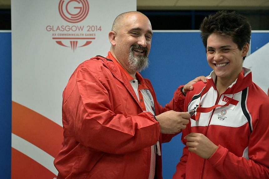 Joseph Schooling (right) celebrating his silver-medal achievement in the 100m butterfly event with his coach Sergio Lopez at the Tollcross International Swimming Centre on July 28, 2014. -- PHOTO: ST FILE