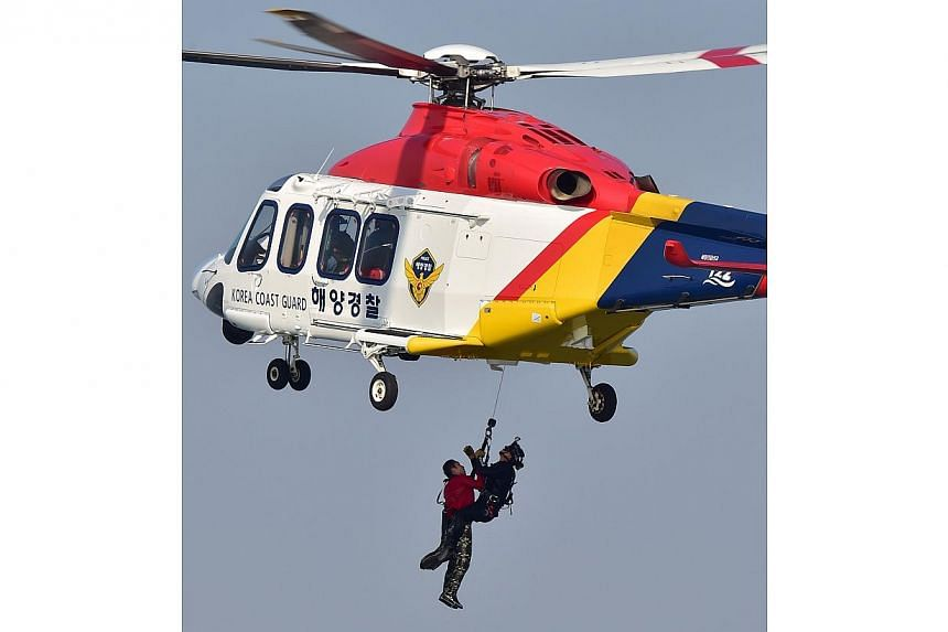 A South Korean Coast Guard helicopter carrying a mock victim during a ferry rescue operation as part of the Safety Korea Exercise, a nationwide anti-disaster drill, off the western port of Incheon on Oct 23, 2014. A massive new government agency to r