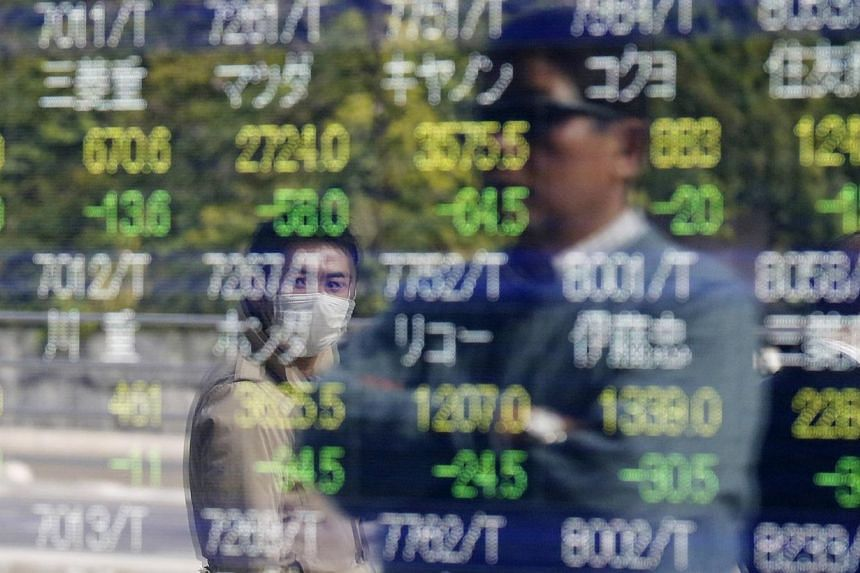 Passers-by are reflected on an electronic stock quotation board outside a brokerage in Tokyo, on Nov 17, 2014. -- PHOTO: REUTERS
