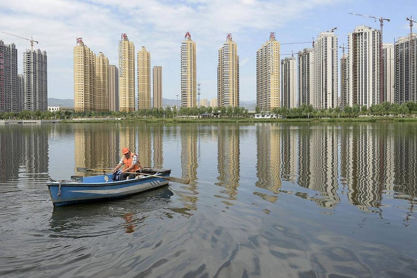 A man rowing a boat on a river in front of properties in Taiyuan, Shanxi province in this July 24, 2014 file photo. Average new home prices in China's 70 major cities fell 2.6 per cent in October from a year earlier, the second consecutive month show