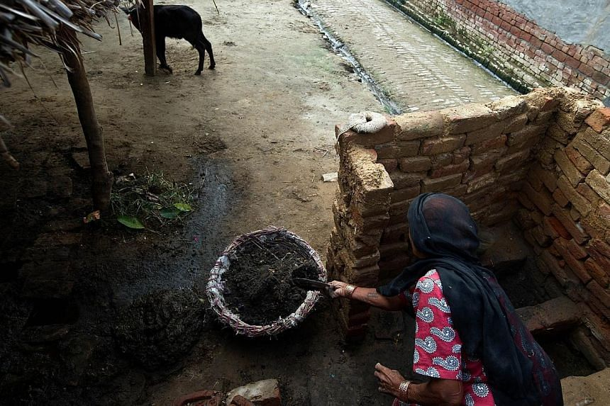 60 year old manual scavenger Kela collects human waste while cleaning a toilet in Nekpur village, Muradnagar in Uttar Pradesh, some 40 kms east of New Delhi.-- PHOTO: AFP