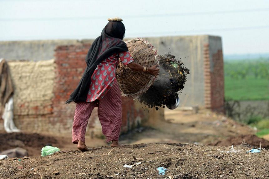 60 year old manual scavenger Kela collects human waste while cleaning a toilet in Nekpur village, Muradnagar in Uttar Pradesh, some 40 kms east of New Delhi. -- PHOTO: AFP