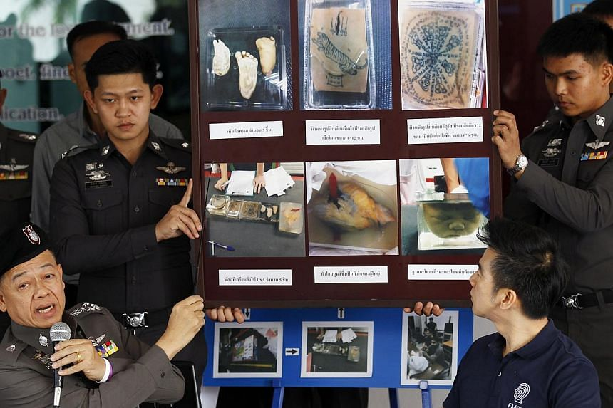 Policemen show pictures of body parts found in parcels as they address reporters in Bangkok on Nov 17, 2014. American Ryan Edward McPherson allegedly stole the infant body parts from a medical museum and tried to courier them to the United States. --