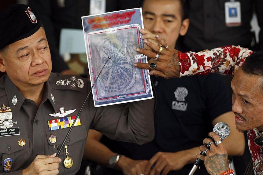 A tattoo expert and a policeman (left) point at one of the pictures of body parts found in parcels as they address reporters in Bangkok on Nov 17, 2014. -- PHOTO: REUTERS