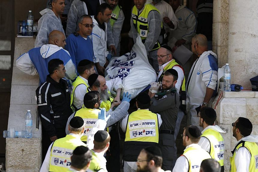 Israeli emergency personnel carry the body of a victim from the scene of an attack at a Jerusalem synagogue on Nov 18, 2014. Pope Francis has condemned the attack and expressed concern about rising tension and violence in the city. -- PHOTO: REUTERS