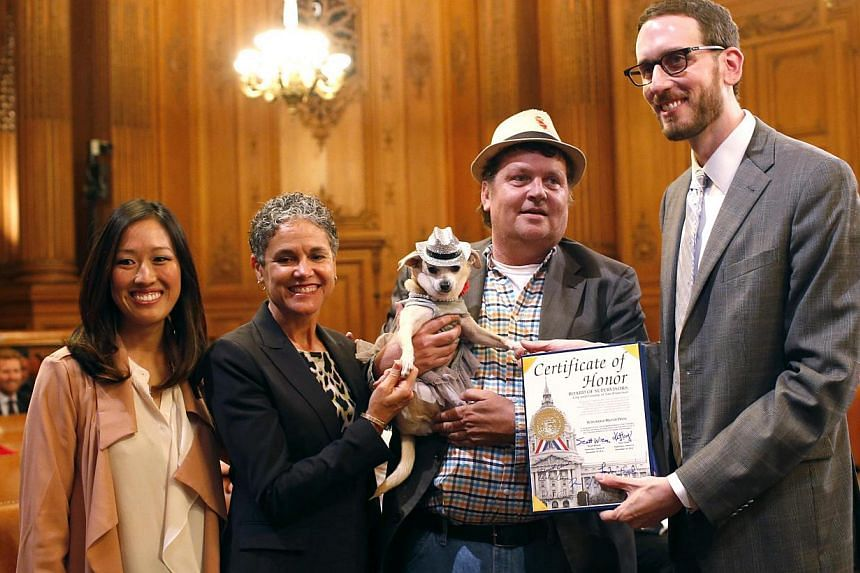(From left) Supervisor Katy Tang, San Francisco Animal Care and Control Acting Director Miriam Saez, Frida, a female Chihuahua, dog owner Dean Clark and Supervisor Scott Wiener pose for a photograph after the San Francisco Board of Supervisors issued