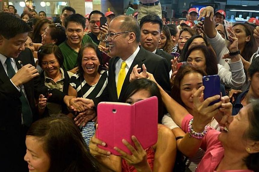 Philippine President Aquino was received like a rock star by a small gathering of Filipinos, who cheered and clamoured to take photos of him as he dined at the Orchard Road shopping mall outlet. -- ST PHOTO: KUA CHEE SIONG