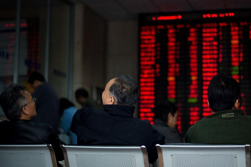 Investors look at a screen showing stock information at a brokerage house in Shanghai on Nov 17, 2014.Foreign buyers used only 20 per cent of their 13 billion yuan (S$2.76 billion) daily quota of Shanghai stocks on Wednesday, Nov 19, as demand