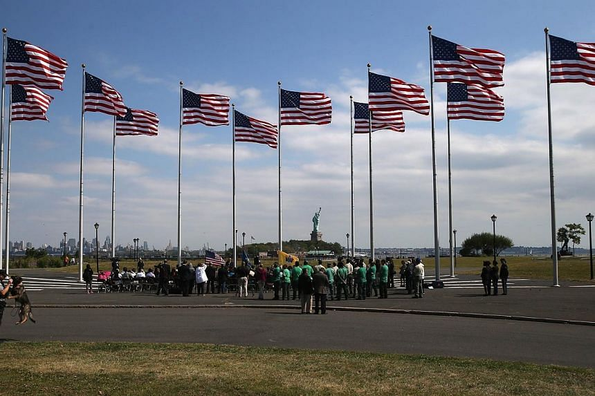 Immigrants prepare to take the oath of citizenship to the United States at a naturalization ceremony at Liberty State Park on Sept 19, 2014, in Jersey City, New Jersey.-- PHOTO: AFP