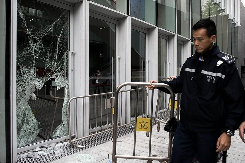A policeman carries a barrier past a broken window of the government headquarters building in the Admiralty district of Hong Kong on Nov 19, 2014, after a small group attempted to break into the city's legislature. -- PHOTO: AFP