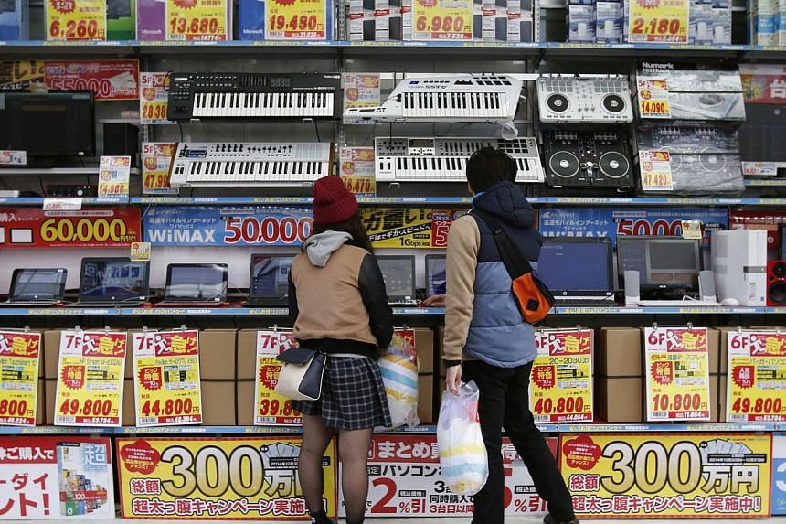 People trying out laptops displayed at an electronics retail store in Tokyo on Nov, 16, 2014. Japan's economy unexpectedly slipped into recession in the third quarter on Nov 17, 2014, setting the stage for Prime Minister Shinzo Abe to delay an unpopu