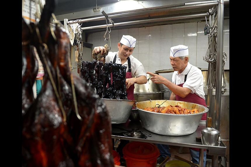 Former Kay Lee Roast Meat Joint owner Ha Wai Kay (above right) training the new chef. Despite the rain yesterday, customers were still queuing to get their fix of roast meats at Kay Lee Roast Meat Joint (above).