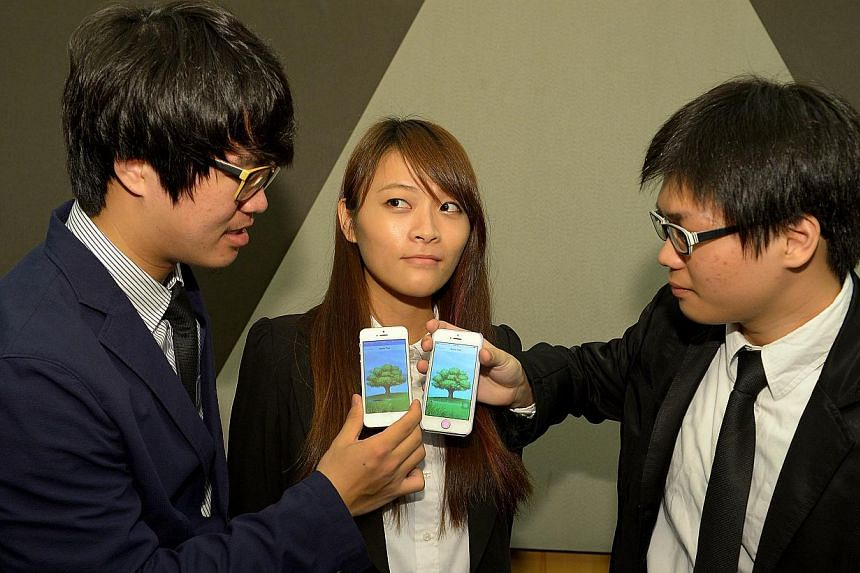 Republic Polytechnic's winning team (from left) Libern Lin Yue Bin, Fang Ling Qing and Lester Yap Jian Le, all 20, displaying their winning app, Apple Tree, which aims to get people to spend more face time with each other. They won a $30,000 grant
