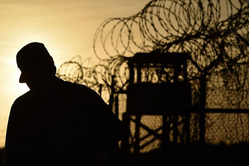 """A US soldier walking next to the razor wire-topped fence at the abandoned """"Camp X-Ray"""" detention facility at the US Naval Station in Guantanamo Bay, Cuba. -- PHOTO: AFP"""