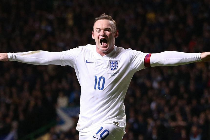 England's striker Wayne Rooney celebrates scoring their third goal during the international friendly football match between Scotland and England at Celtic Park in Glasgow, Scotland, on Nov 18, 2014. -- PHOTO: AFP