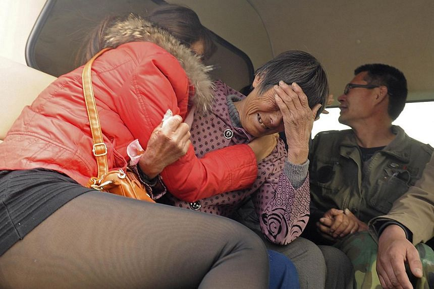 Relatives of kindergarten children, who died after the van they were travelling in ran into a truck, cry in Penglai, Shandong province on Nov 19, 2014. -- PHOTO: REUTERS