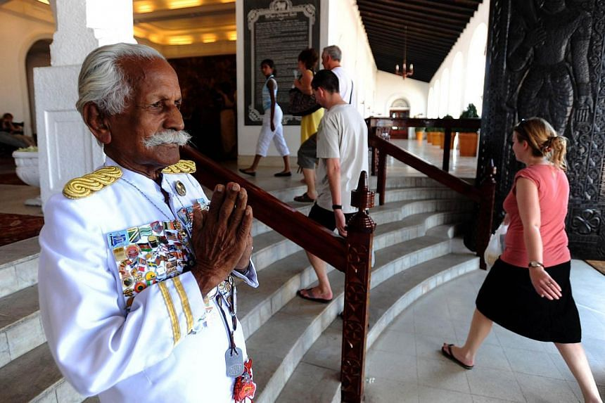 A photograph taken on Feb 6, 2010, shows Sri Lanka's legendary doorman, Kottarapattu Chattu Kuttan holding his palms in a traditional greeting, outside the island's historic 146-year-old Galle Face Hotel in Colombo. Sri Lanka's oldest hotel doorman a