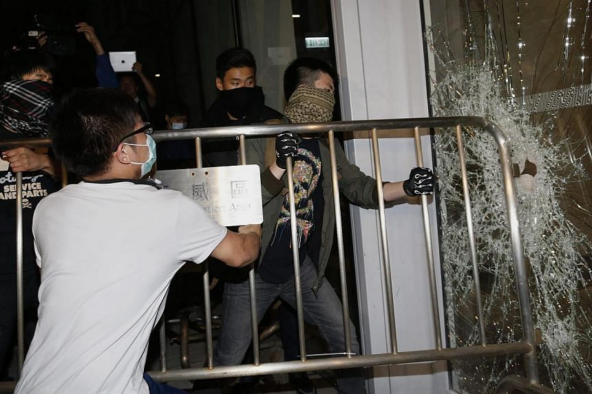 """Masked pro-democracy protesters try to break into the Legislative Council through a glass window with a fence in Hong Kong early Nov 19, 2014, in response to an earlier clear up by bailiffs on part of the """"Occupy Central"""" protest site. -- PHOTO: REUT"""