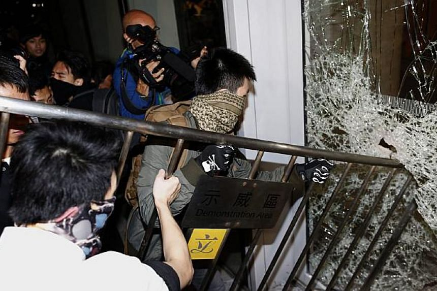 """Masked pro-democracy protesters try to break with a fence a glass window of the Legislative Council in Hong Kong early Nov 19, 2014, in response to an earlier clear up of part of the """"Occupy Central"""" protest site. -- PHOTO: REUTERS"""