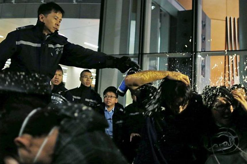 """Pro-democracy protesters are pepper sprayed by a policeman as they try to break into the Legislative Council in Hong Kong early Nov 19, 2014, in response to an earlier clear up by bailiffs on part of the """"Occupy Central"""" protest site. -- PHOTO: REUTE"""