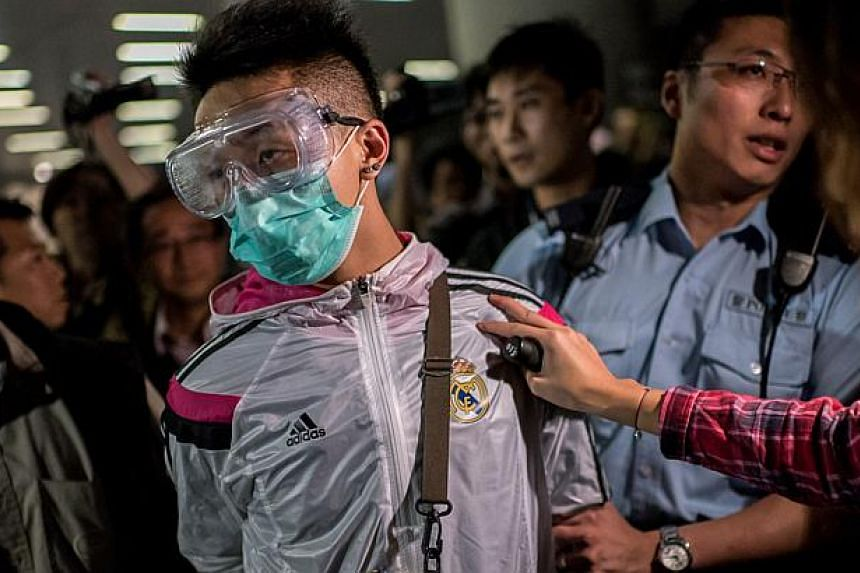 Police detain a man wearing protective as pro-democracy protesters faced-off with police outside the central government offices in the Admiralty district of Hong Kong on Nov 19, 2014. -- PHOTO: AFP