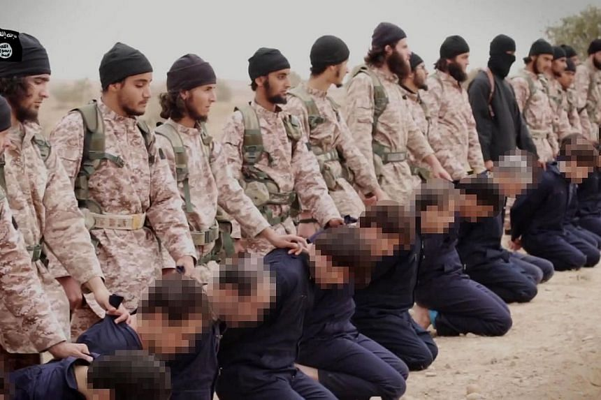 An still taken from a propaganda video released on Nov 16, 2014 by al-Furqan Media allegedly shows members of the Islamic State jihadist group preparing the simultaneous beheadings of men described as Syrian military personnel. -- PHOTO: AFP/ HO/ AL-