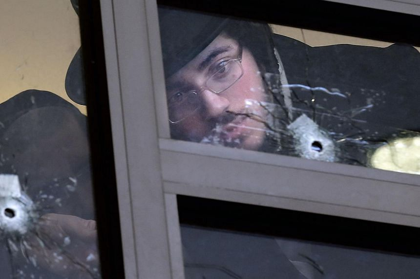 Ultra Orthodox Jews on Nov 19, 2014look at bullet holes in the main window of a synagogue in Jerusalem which was attacked the previous day by two Palestinians armed with a gun and meat cleavers, leaving five Israeli worhipers killed. -- PHOTO: