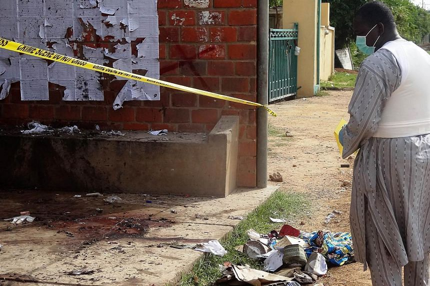 A file picture taken on July 30, 2014 show a police detective inspecting the site of a suicide blast outside the central administration building of the Kano State Polytechnic institute in the northern Nigerian city of Kano, which killed at least six