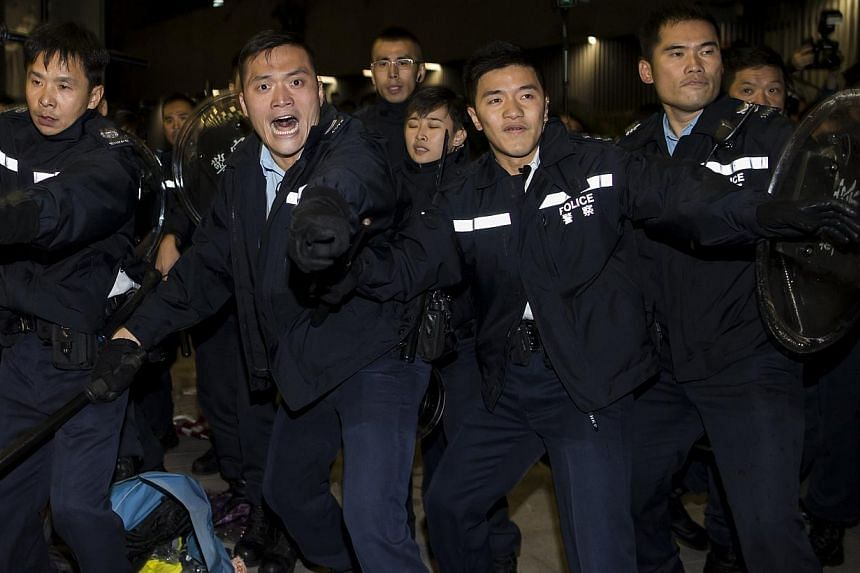 Police shout to protesters as they try to break into the Legislative Council in Hong Kong early on Nov 19, 2014. -- PHOTO: REUTERS