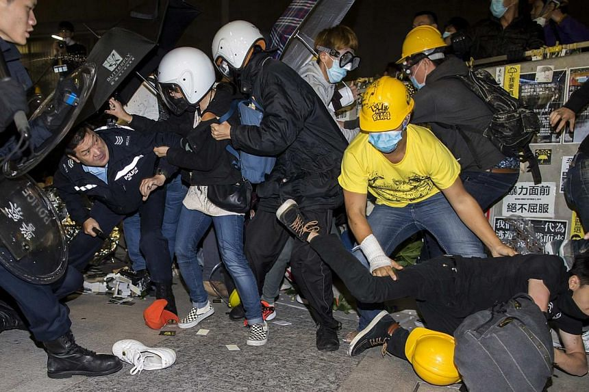 A protester falls on the ground as they are chased by riot police outside the Legislative Council in Hong Kong early on Nov 19, 2014. -- PHOTO: REUTERS