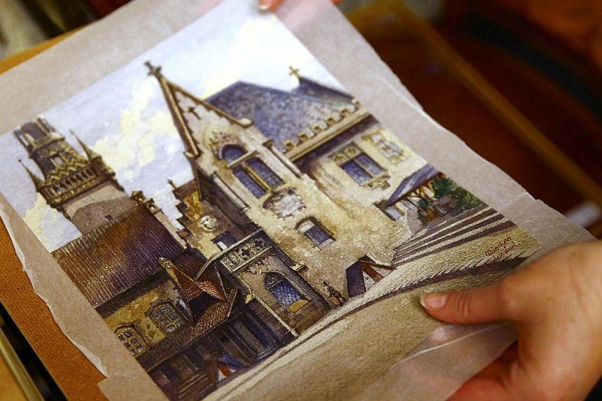 An employee puts away a watercolour of the old registry office in Munich by former German dictator Adolf Hitler at Weidler auction house in Nuremberg Nov 18, 2014. The watercolour, which was painted by Hitler around 1914 and includes an original bill