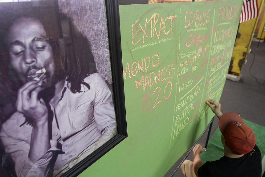 A portrait of reggae legend Bob Marley hangs next to a menu of marijuana products at the medical marijuana farmers market at the California Heritage Market in Los Angeles. His family and a Seattle-based private equity firm on Nov 18, 2014, said they