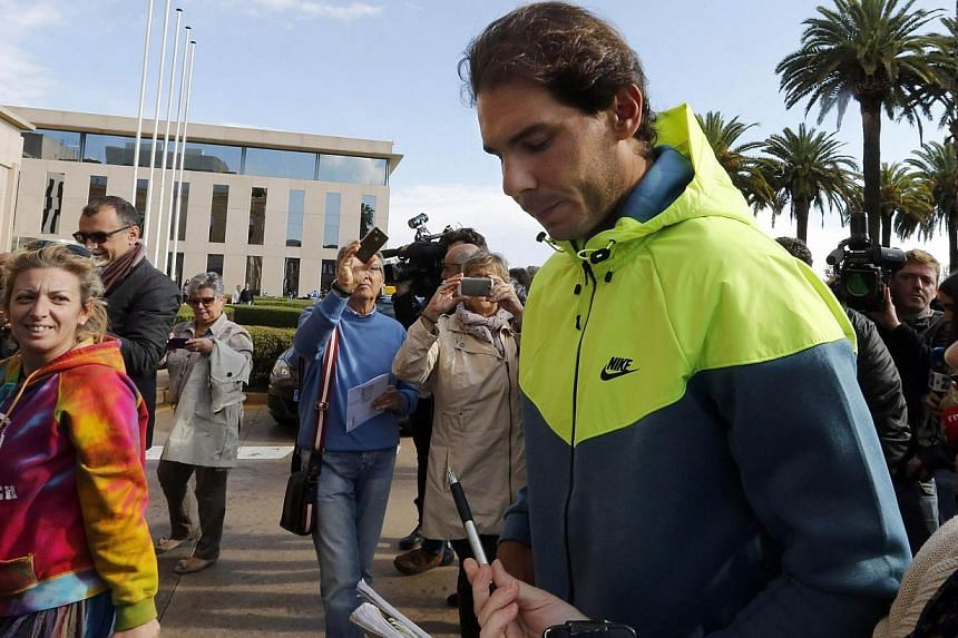 Spanish tennis player Rafael Nadal signs an autograph as he leaves the hospital after appendicitis surgery in Barcelona on Nov 5, 2014. Nadal is aiming to be fit for the Australian Open in January as he recovers from an appendicitis operation, the Sp