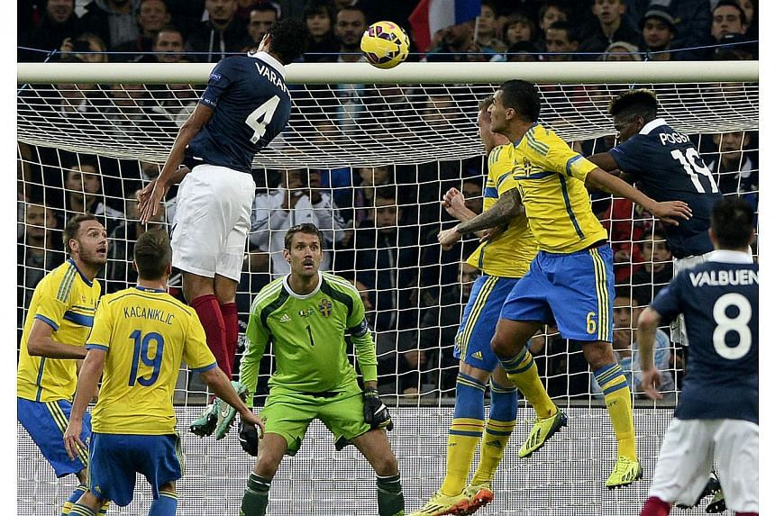 French defender Raphael Varane (left) jumps for the ball during the friendly football match France vs Sweden at the Velodrome stadium in Marseille, southern France on Nov 18, 2014. -- PHOTO: AFP