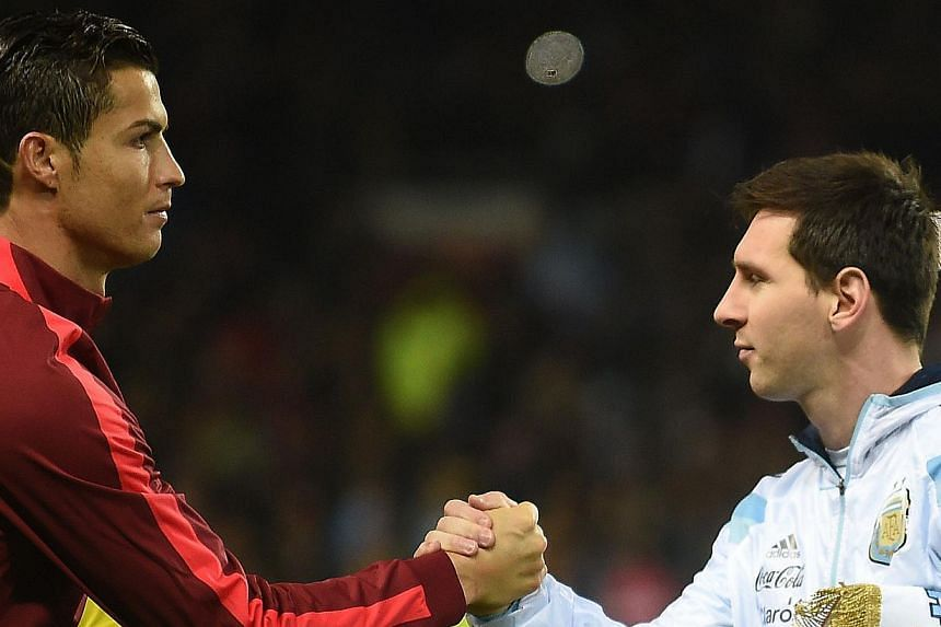 Argentina striker Lionel Messi (right) shakes hands with Portugal's striker Cristiano Ronaldo (left) ahead of kick off of the international friendly football match between the Argentina and Portugal at Old Trafford in Manchester on Nov 18, 2014. -- P