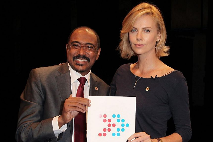 Executive Director of UNAIDS Michel Sidibe (left) and actress Charlize Theron attend the launch of UNAIDS New Fast Track Report ahead of World AIDS Day 2014 at UCLA on Nov 18, 2014. -- PHOTO: AFP