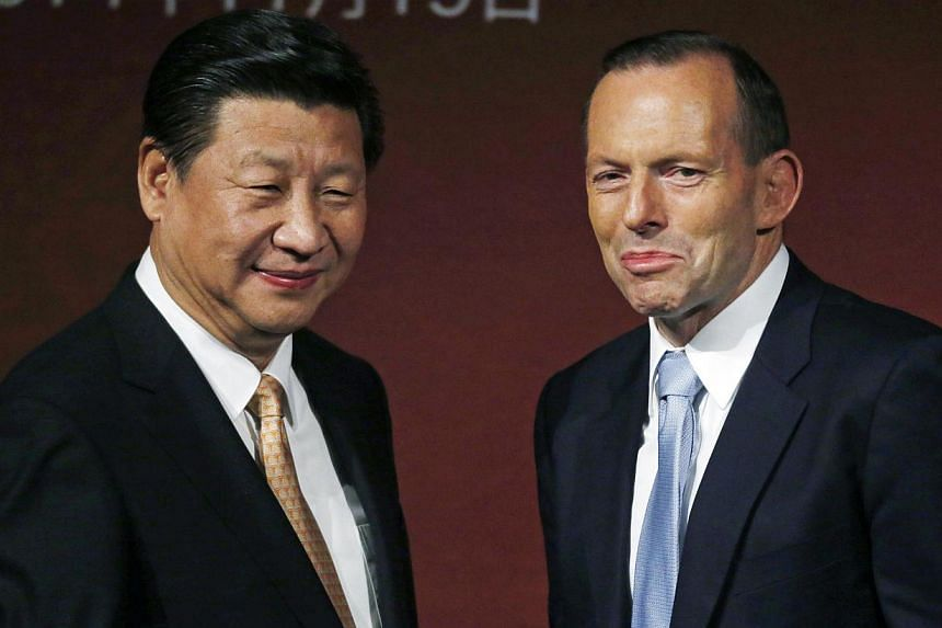 China's President Xi Jinping (left) and Australia's Prime Minister Tony Abbott are pictured on stage after addressing the Australia-China state and provincial leaders forum in Sydney, Australia on Nov 19, 2014. -- PHOTO: REUTERS