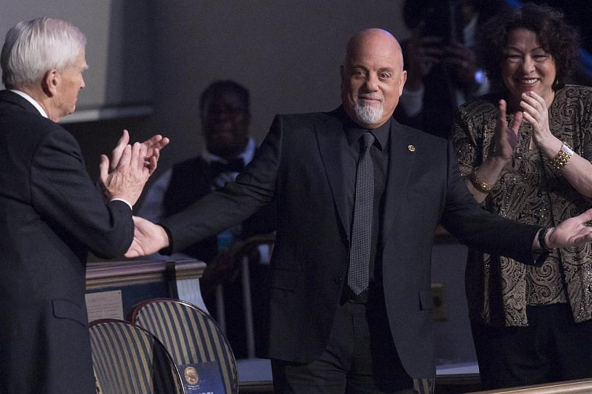 Singer Billy Joel, recipient of the 2014 Library of Congress Gershwin Prize for Popular Song, arrives for a tribute concert in his honour alongside US Supreme Court Justice Sonia Sotomayor (right) and James Billington (left), Librarian of Congress, a