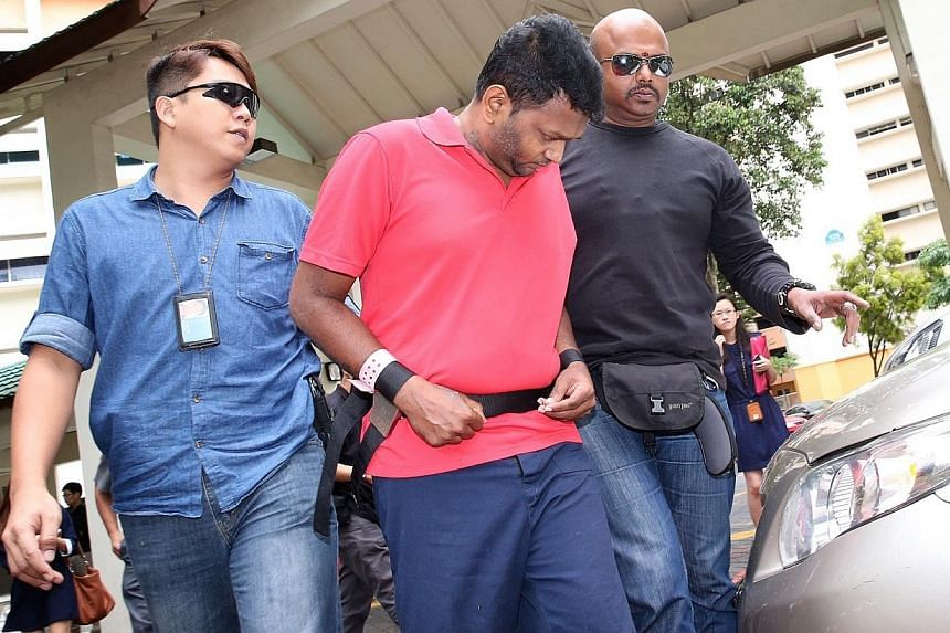 Annadurai Raman (in red), who was charged in connection with robbing money changer Ali Yousouf Saiboo of $600,000, took police to Block 125, Geylang East Avenue 1, to give a recount of the alleged incident on Nov 18, 2014.Two of the men alleged