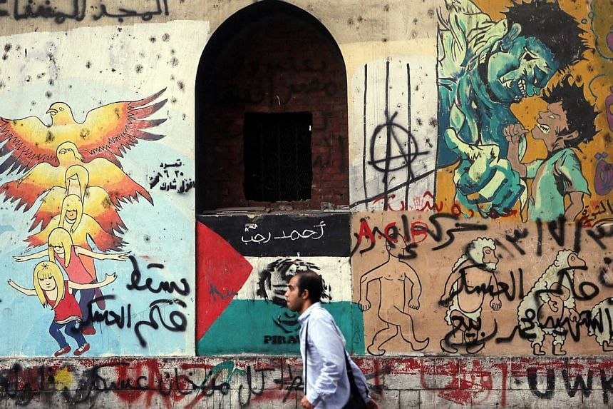 A man walks past graffiti denouncing the Interior and Defence Ministry and members of the Muslim Brotherhood, along Mohamed Mahmoud Street, during the third anniversary of violent and deadly clashes near Tahrir Square in Cairo on Nov 19, 2014. -