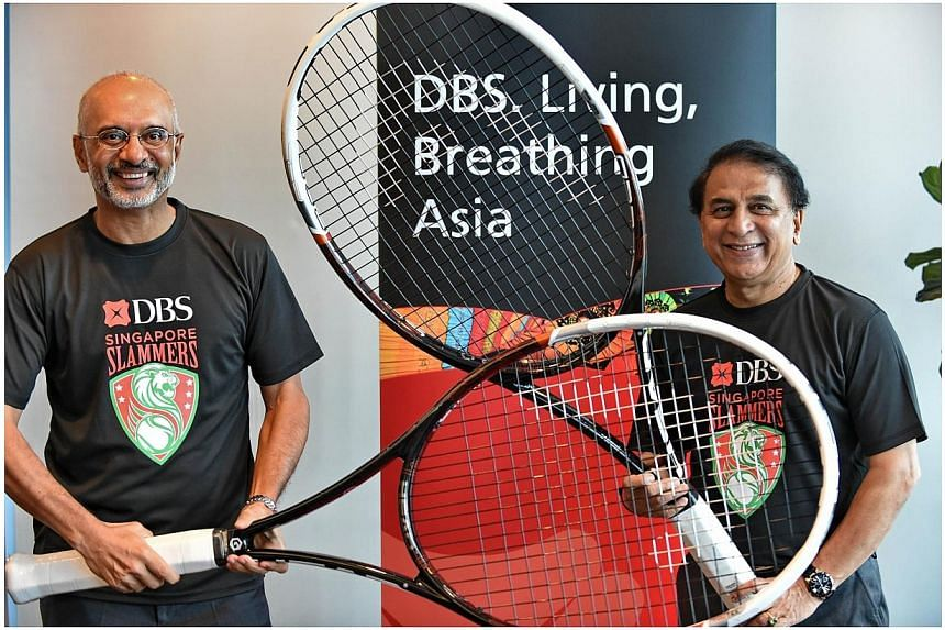 Chairman of Singapore Slammers and internationally acclaimed cricketer Sunil Gavaskar (right) and Piyush Gupta (left), CEO of DBS group, pose with very large tennis rackets after a press conference in Singapore on Nov 20, 2014. Local bank DBS an
