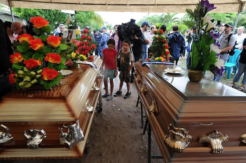 The coffins of former Miss Honduras World Maria Jose Alvarado, 19, and her sister Sofia Trinidad remain in front of their home during their wake on Nov 20, 2014, in Santa Barbara, 200 km north of Tegucigalpa. -- PHOTO: AFP