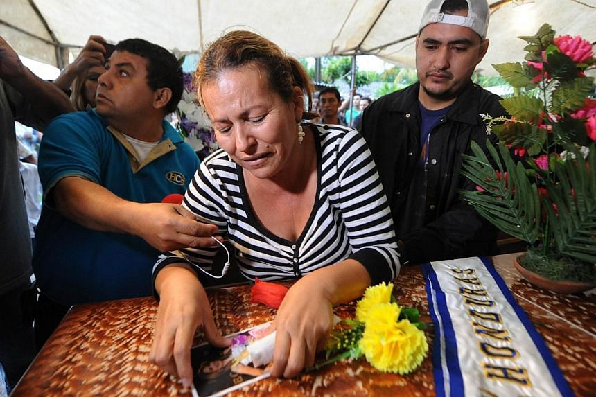 Teresa Munoz watches a picture of her daughter, former Miss Honduras World Maria Jose Alvarado, 19, over her coffin on Nov 20, 2014, in Santa Barbara, 200 km north of Tegucigalpa. -- PHOTO: AFP