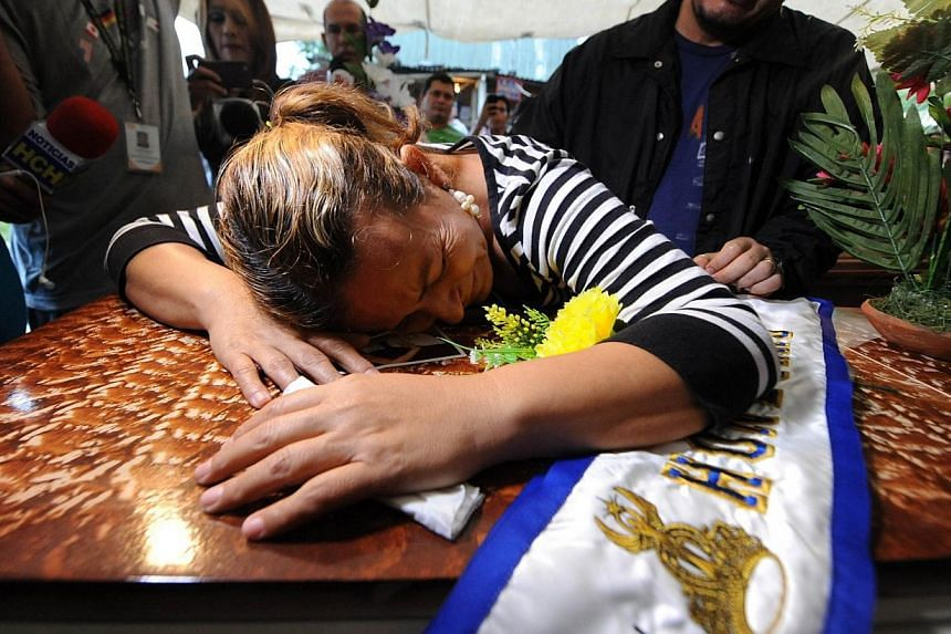 Teresa Munoz cries over the coffin of her daughter, former Miss Honduras World Maria Jose Alvarado, 19, on Nov 20, 2014, in Santa Barbara, 200 km north of Tegucigalpa. -- PHOTO: AFP