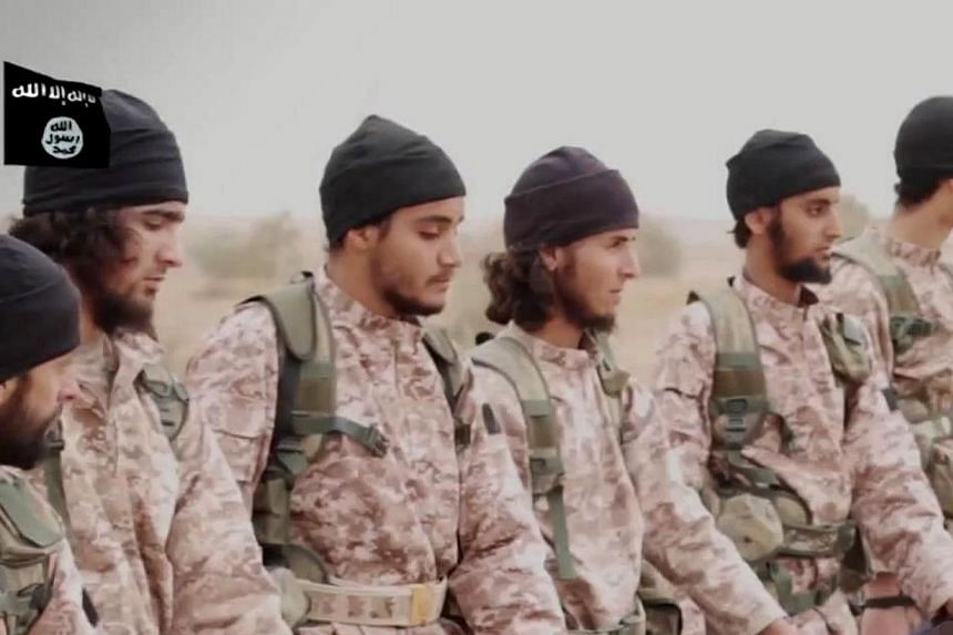 An image grab taken from a propaganda video released on Nov 16, 2014, by al-Furqan Media allegedly shows members of the Islamic State jihadist group preparing the simultaneous beheadings of at least 15 men described as Syrian military personnel. -- P