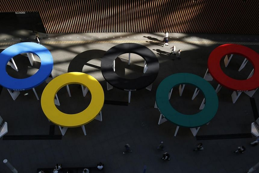 People walk past Olympic ring structures, which are part of booths at a photo exhibition on the history of Japanese participation in the previous Olympic games and its journey to the 2020 Olympics, at a commercial building in Tokyo's business distric